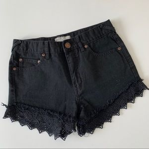 Free People black denim shorts with lace trim